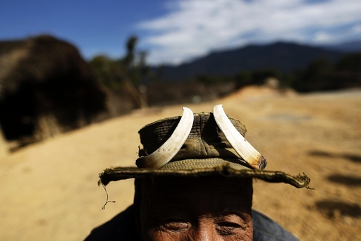 A man who claims to be 100 years old wears a hat adorned with wild boar tusks in Donhe township in the Naga Self-Administered Zone