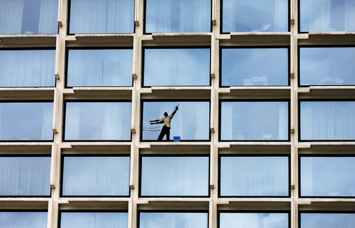 A worker cleans the windows of a luxury hotel in Colombo