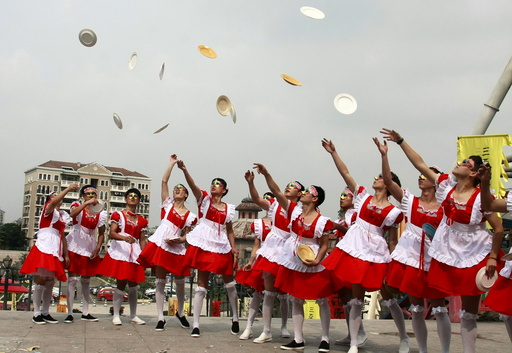 Male staff members of an amusement park wearing maid costumes throw chinaware into the air to be smashed during an event promoting their stress-release activities to mark World Mental Health Day, in Hangzhou