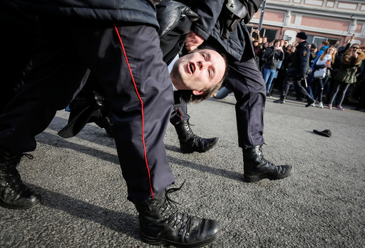 Law enforcement officers detain an opposition supporter during a rally in Moscow, Russia
