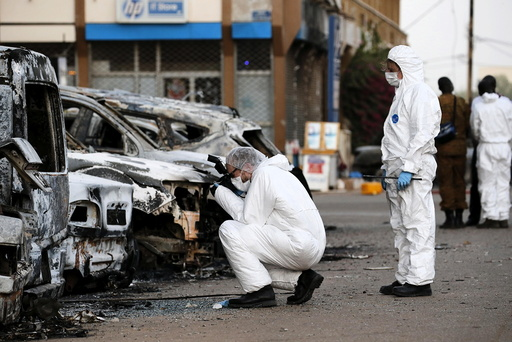French police inspect burned vehicles outside the Splendid Hotel in Ouagadougou