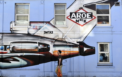 A resident walks past a house covered with a painted mural in Brighton