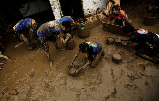 Volunteers clean a flooded home after rivers breached their banks due to torrential rains causing flooding and widespread destruction in Cajamarquilla, Lima