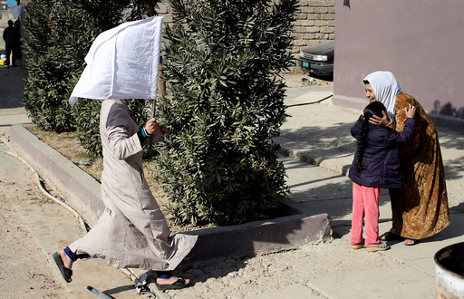 A woman holds up a white flag as she runs to greet her relative in Mosul