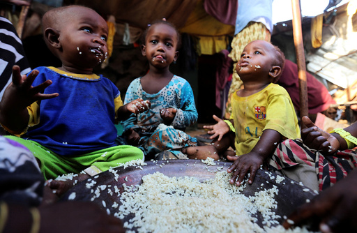 Internally displaced Somali children eat boiled rice outside their family's makeshift shelter at the Al-cadaala camp in Somalia's capital Mogadishu