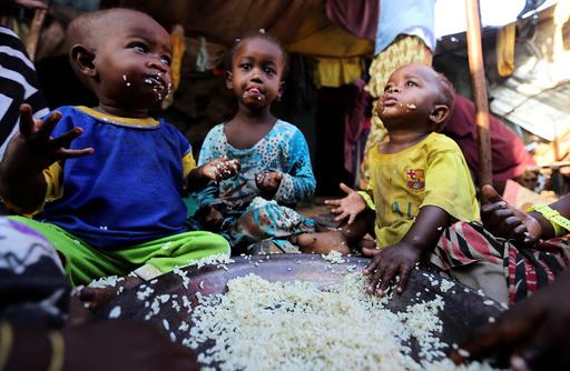 Internally displaced Somali children eat boiled rice outside their family's makeshift shelter at the Al-cadaala camp in Somalia's capital Mogadishu