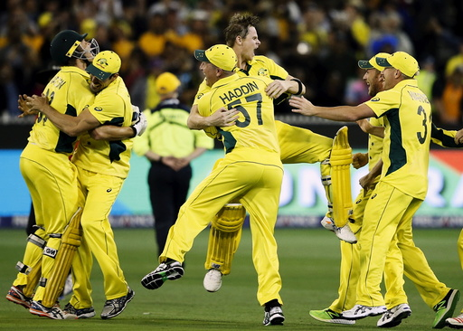 Australian players celebrate after defeating New Zealand in their Cricket World Cup final match at the MCG