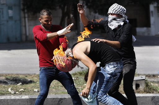 Palestinian protesters put out a fire burning on a compatriot, caused by a molotov cocktail which he was trying to hurl at Israeli troops during clashes in the West Bank city of Hebron