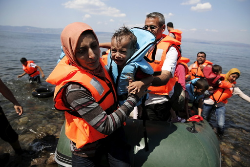 A Syrian refugee carries her baby as she arrives with other Syrian refugees on a dinghy on the island of Lesbos