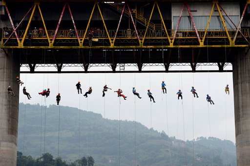 People slide down a rope from a bridge during a rescue training in Chongqing