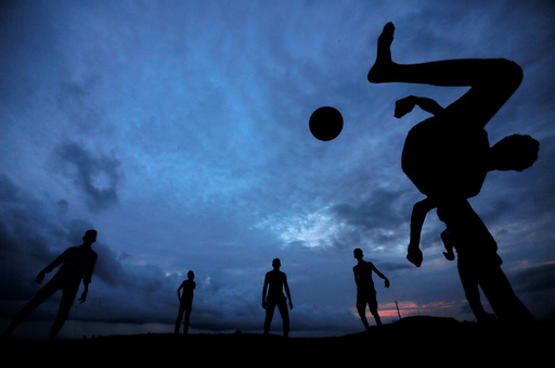 A boy kicks a ball as he plays soccer with his friends at Galle Dutch Fort in Galle