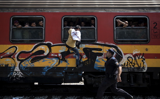 Policeman tries to stop a migrant from boarding a train through a window at Gevgelija train station in Macedonia, close to the border with Greece