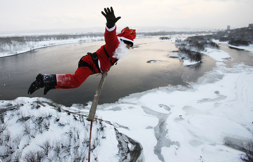 A man dressed as Father Frost, Russian equivalent to Santa Claus, jumps makes a bungee jump from a bridge across the Yenisei River in the Siberian city of Krasnoyarsk