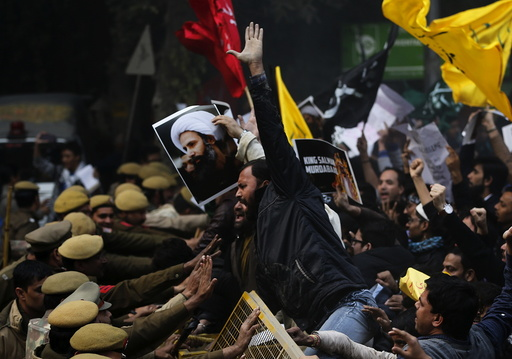 Shi'ite Muslims try to cross a barricade during a protest against the execution of cleric Nimr al-Nimr, who was executed along with others in Saudi Arabia, in front of Saudi Arabia embassy in New Delhi