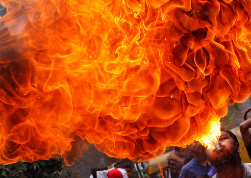 A Hindu devotee performs a stunt with fire during a rehearsal for the annual Rath Yatra in Ahmedabad