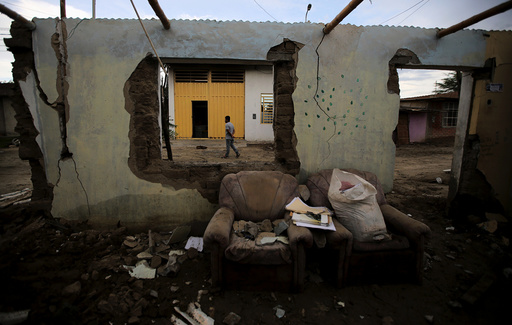 A man walks next to a flooded home damaged after heavy rain in Castilla district of Piura