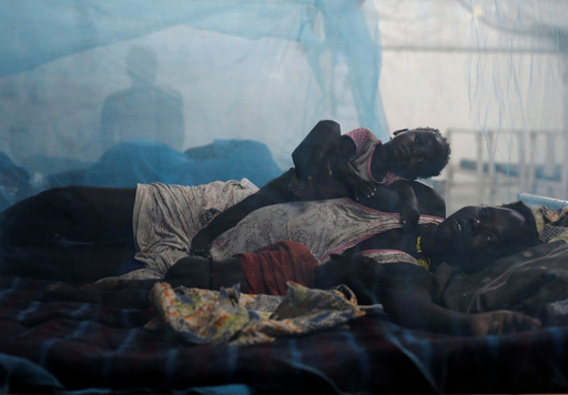 A woman rests in bed with her children in the paediatric ward at the Medecins Sans Frontieres (MSF) hospital inside the UNMISS base in Bentiu, Rubkona County