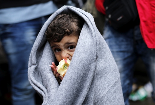 A migrant child eats an apple as he waits next to the border crossing with Croatia near the village of Berkasovo