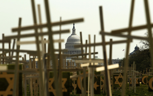With the U.S. Capitol in the background, crosses symbolizing grave markers are placed upon the National Mall in Washington
