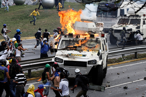 Demonstrators clash with a riot police armored car in Caracas