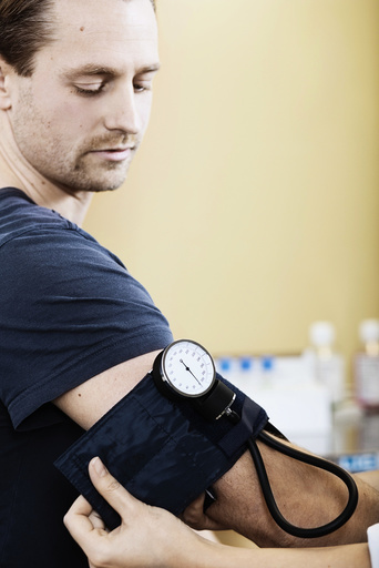 Doctor putting blood pressure cuff on male patient's arm in clinic
