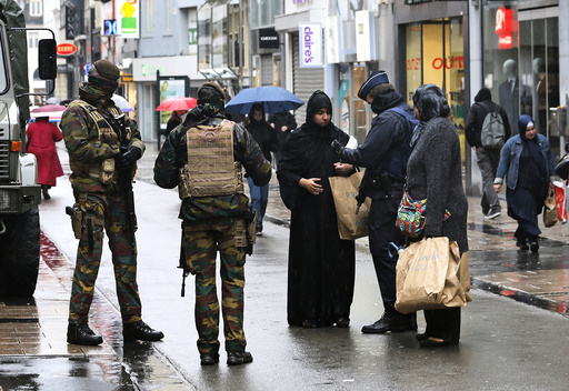Belgian soldiers and a police officer control documents of a woman in a shopping street in central Brussels after security was tightened in Belgium following the fatal attacks in Paris