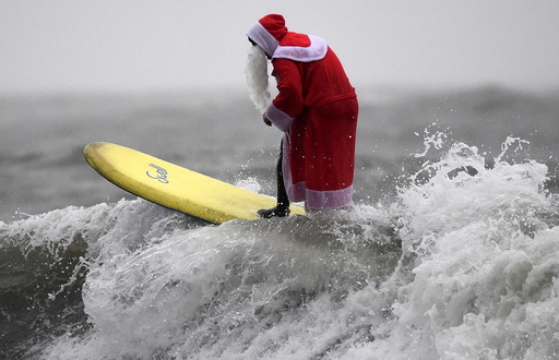 A member of the Langland Board Surfers group takes part in a Surfing Santa competition at Langland Bay in Gower