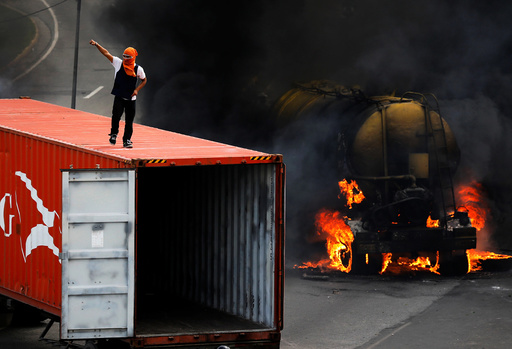 Demonstrator stands on top of a truck set on fire to build a barricade while rallying against Venezuela's President Nicolas Maduro's Government in Caracas
