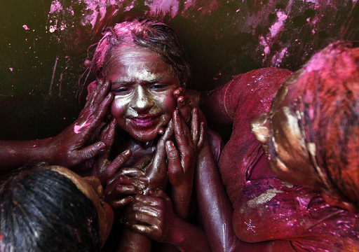 A girl reacts as other girls apply coloured paint on her face during Holi celebrations in Chennai