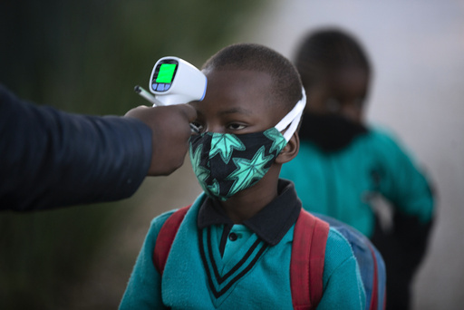 En elev får sjekket temperaturen på vei inn i skolen i Johannesburg. Landet har startet å åpne opp, til tross for at det nå rapporteres om 10.000 nye smittetilfeller på ett døgn. Foto: Denis Farrell / AP / NTB scanpix