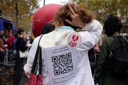 En fransk helsearbeider protesterer mot Frankrikes vaksinemandat. På ryggen hennes står det «Nei til QR koder, nei til koronasertifikat». Foto: François Mori / AP / NTB