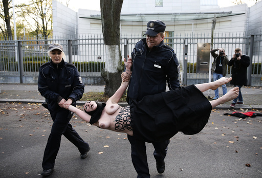 Police detain activist of women's rights group Femen during protest outside the Iranian embassy in Berlin