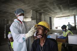 En bygningsarbeider blir testet for koronavirus på en byggeplass i New Delhi torsdag. Smittetallene i India er nå på et lavere nivå enn på lenge. Foto: AP / NTB