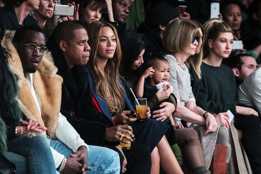 Kim Kardashian attempts to calm her daughter, North, as they watch a presentation of Kanye West's Fall/Winter 2015 partnership with Adidas at New York Fashion Week