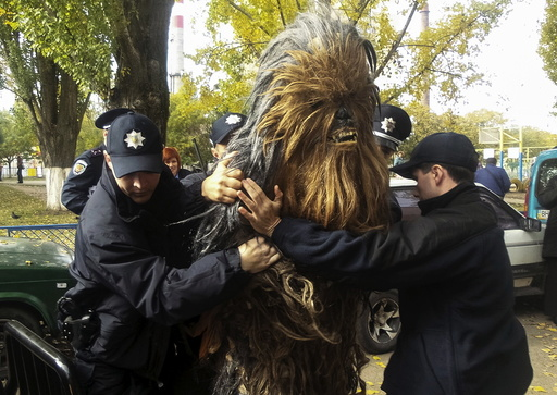 Policemen detain a person dressed as Star Wars character Chewbacca during a regional election near a polling station in Odessa
