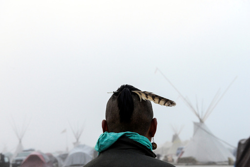 A man from the Muskogee tribe looks at the Oceti Sakowin shrouded in mist during a protest against the Dakota Access pipeline near the Standing Rock Indian Reservation near Cannon Ball, North Dakota