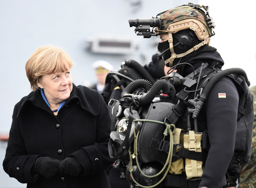 German Chancellor Merkel looks at a combat diver during her visit to Naval Base Command in Kiel
