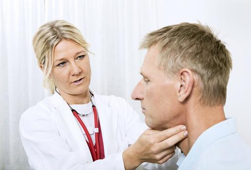 Doctor touching throat