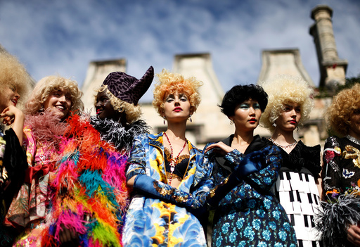 Models pose against the backdrop of an old sandstone chapel during a fashion show for the label Romance Was Born on the waterfront of Sydney Harbour during Australian Fashion Week, Sydney