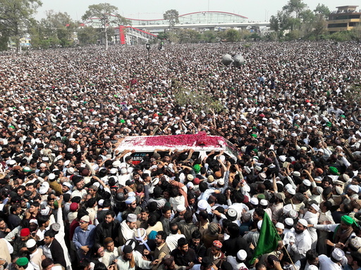 Mourners throw flower petals on an ambulance carrying the body of Mumtaz Qadri to his funeral at Liaquat Bagh in Rawalpindi
