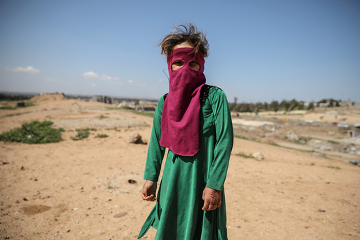 An Iraqi girl stands on a hill close to her house in eastern Mosul