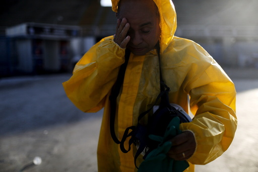 Municipal worker touches his face as he finishes spraying insecticide at Sambodrome in Rio de Janeiro