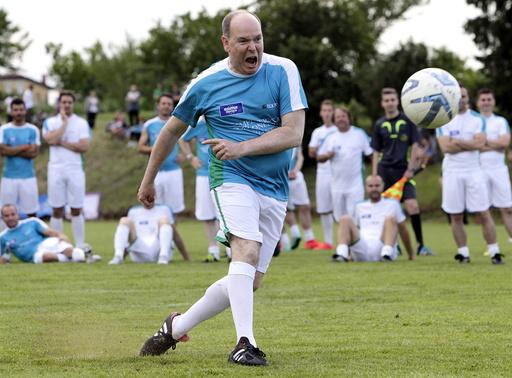Prince Albert II of Monaco kicks the ball during a charity soccer match in Bilje