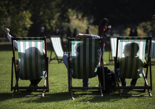 People are silhouetted against their deck chairs as they pose for a