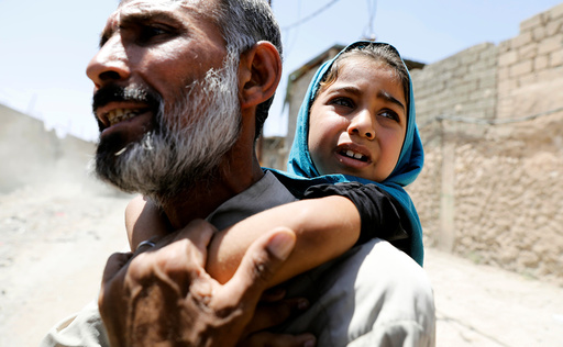 A man carries his daughter on his back after fleeing their home due to fighting between the Iraqi forces and Islamic State militants in Mosul's al-Zanjili's district in Iraq