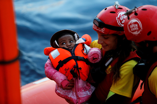 A crew member of MV Open Arms carries a migrant baby before passing it to crew members of MV Aquarius during a mid-sea transfer of migrants in the central Mediterranean off the coast of Libya