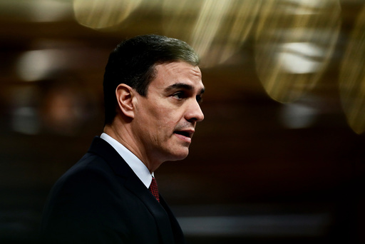 Spain's Prime Minister Pedro Sanchez speaks in a nearly empty parliament while the majority of lawmakers follow the session online before a vote to approve the extension of the national lockdown in Madrid, Spain, Wednesday, March 25, 2020. Spain released new figures of the official number of deaths in Spain because of the COVID-19 coronavirus, surpassing China's death toll. The new coronavirus causes mild or moderate symptoms for most people, but for some, especially older adults and people with existing health problems, it can cause more severe illness or death. (Mariscal, Pool photo via AP)
