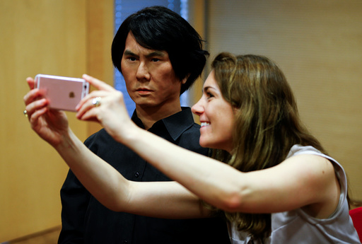 A woman takes a selfie with life-size humanoid robot HI-4 in Duesseldorf