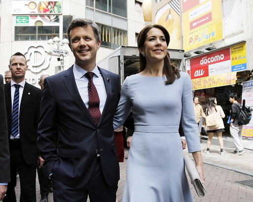 Denmark's Crown Prince Frederik and his wife Crown Princess Mary walk on a street at Shibuya shopping district in Tokyo