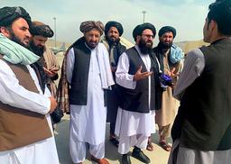 Taliban-talsmann Zabihullah Mujahid, her flankert av andre Taliban-medlemmer, holdt en improvisert pressekonferanse ute på rullebanen på flyplassen i Kabul tirsdag. Foto: Kathy Gannon / AP / NTB